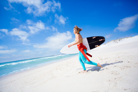 Surfer girl holding a surfboard at the beach photo