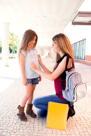 shool: Mother saying goodbye to her daughter at shool Stock Photo