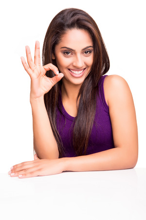 Beautiful young woman showing Ok sign over white