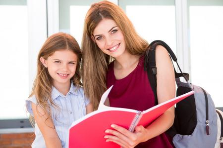 sketchbook: Little school girl showing sketchbook to her mother Stock Photo