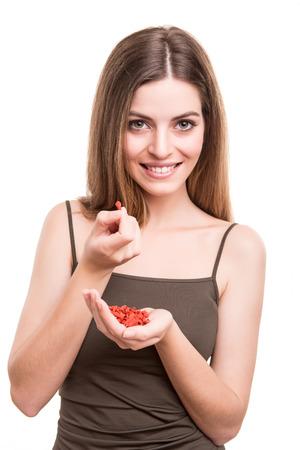 goji berry: Cute girl eating a bunch of goji berries Stock Photo