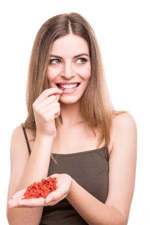 frutas secas: Chica linda que come un montón de bayas del goji