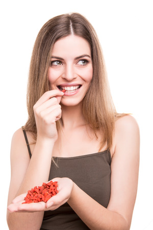 Cute girl eating a bunch of goji berries Stock Photo