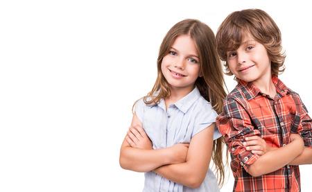 niño y niña: Cool kids pequeños que presentan sobre el fondo blanco Foto de archivo