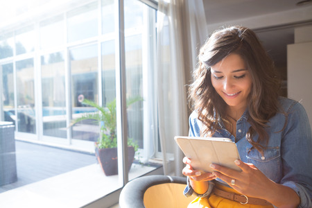 Fashion woman using tablet with sunbeams and lens flare photo