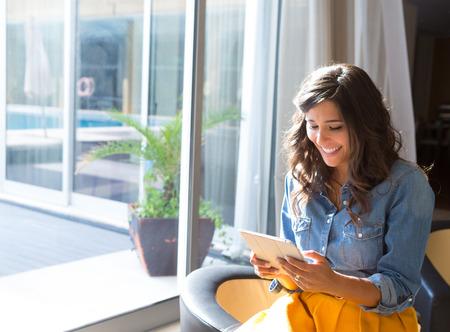falda: Mujer de moda que usa la tableta con rayos y reflejos en la lente