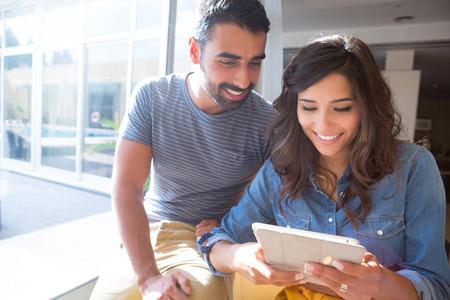 Fashion couple à l'aide d'une tablette avec des rayons de soleil et lens flare