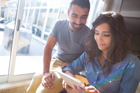 cafe internet: Pares de la manera con una tableta con rayos y reflejos en la lente