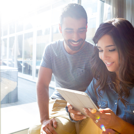 Fashion couple using a tablet with sunbeams and lens flare Stock Photo