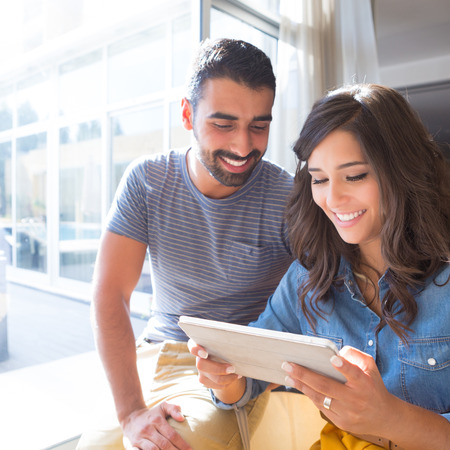 Fashion couple using a tablet with sunbeams and lens flare photo