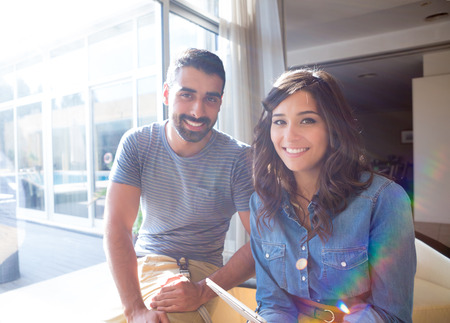 casual caucasian: Fashion couple using a tablet with sunbeams and lens flare Stock Photo