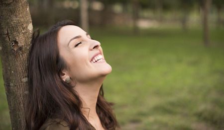 Woman with happy expression relaxing on meadow Stock Photo