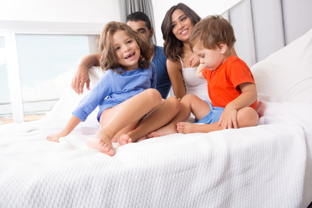 Happy family enjoying the morning in bed Stock Photo