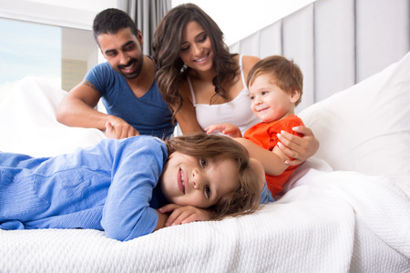 Happy family enjoying the morning in bed Banco de Imagens