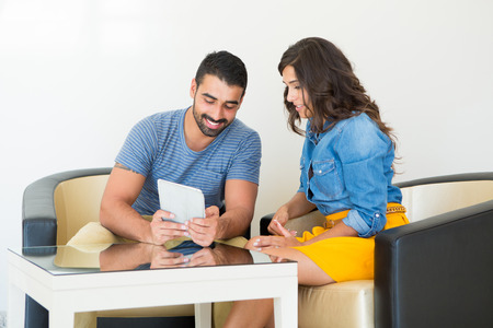 Fashion couple sitting together and using a tablet photo