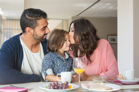 latin family: Child having breakfast with her mother and father