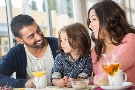 Child having breakfast with her mother and father
