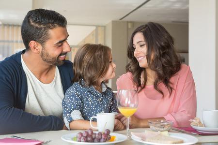 niños desayunando: Niño desayunando con su madre y padre