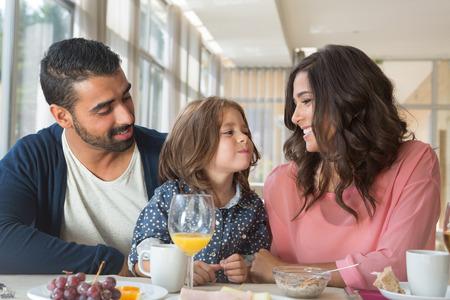 Kind dat ontbijt met haar vader en moeder Stockfoto