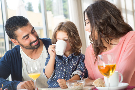 Child having breakfast with her mother and father photo