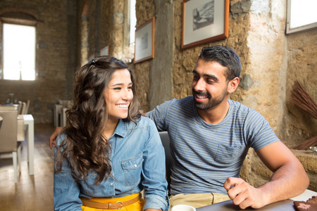 two: Young couple talking in restaurant and cafe