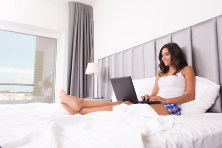Woman lying in bed with her laptop photo