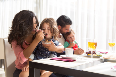 Young latin family having breakfast with kids photo