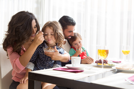 Young latin family having breakfast with kids Stock Photo