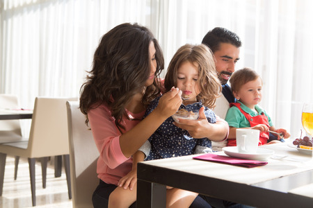 latin family: Young latin family having breakfast with kids Stock Photo
