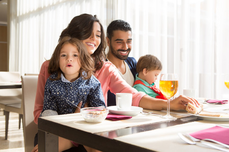 latin: Young latin family having breakfast with kids Stock Photo