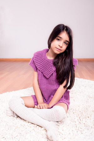 Girl sitting on the floor wearing weater and socks photo