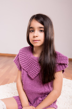 Girl sitting on the floor wearing sweater and socks photo