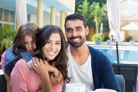 プールに近いリラックスした美しいラテン系家族