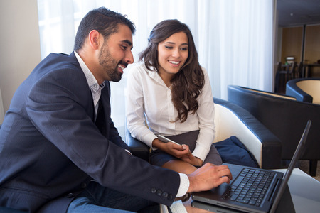 Young business couple meeting with tech devices Stock Photo