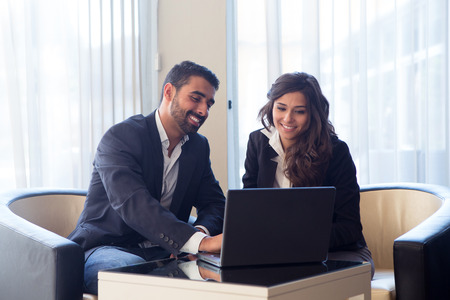 corporate meeting: Young business couple meeting with tech devices Stock Photo