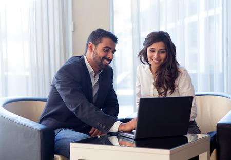 Young Business paar ontmoeting met tech apparaten
