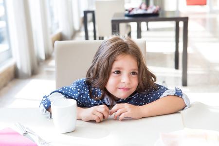 niños desayunando: Niño lindo tener un delicioso desayuno