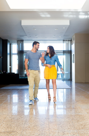 Fashion couple walking through modern building hall photo