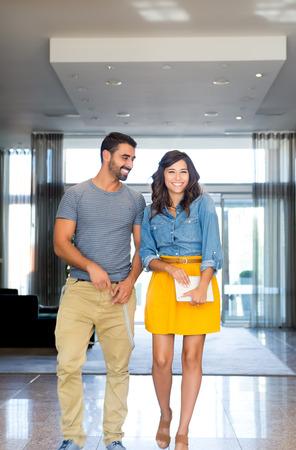 denim skirt: Fashion couple walking through modern building hall