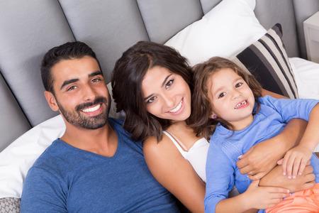 침대에서 아침을 즐기는 행복한 가족