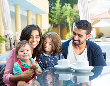 latin family: Happy family sitting together close to the pool Stock Photo