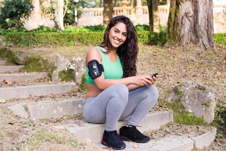 armband: Fitness woman using smartphone in the park Stock Photo