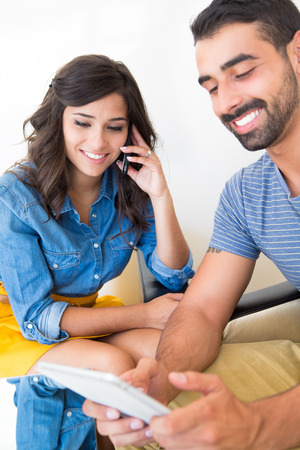 Young fashion couple using smartphone and tablet photo