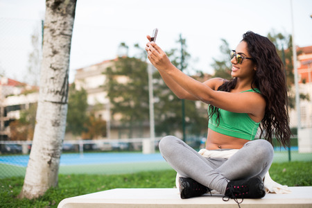 Sporty woman taking selfies at the park photo