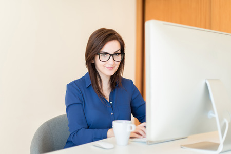 Woman using a desk computer at office