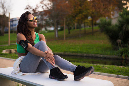 armband: Fitness woman runner relaxing  in the city park
