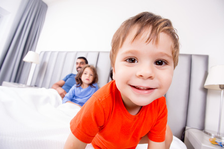 Close up of funny boy playing in bed with family photo