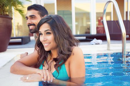 descansando: Pares hermosos que se divierten en la piscina