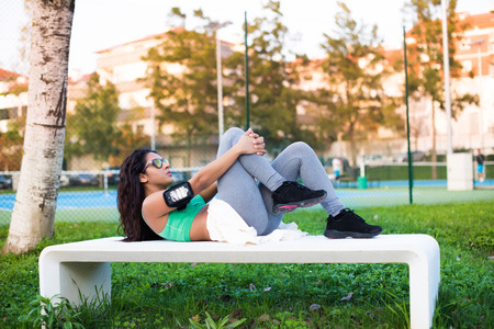 Fitness woman doing abs exercises in the city park photo