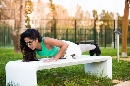 Fitness woman doing pushup exercises in the city park photo